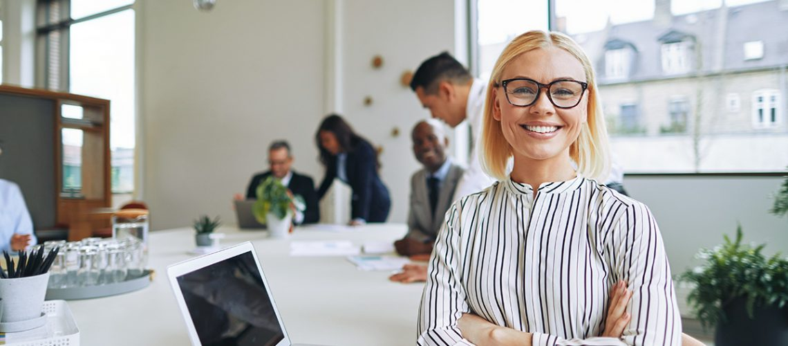 Smiling young businesswoman sitting with her arms crossed at a boardroom table with colleagues working in the background